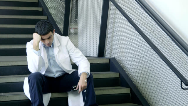 male doctor on staircase - head in hands stock videos and b-roll footage