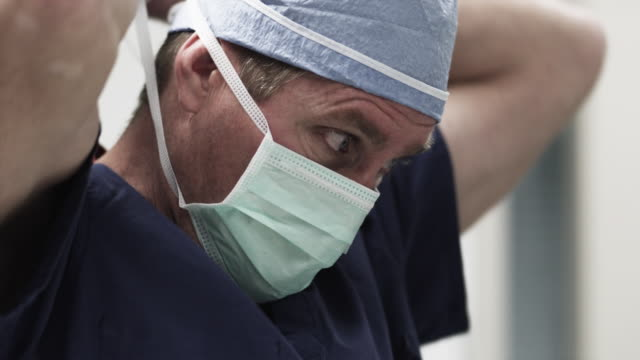 cu male doctor putting on surgical mask / payson, utah, usa - 保護マスク点の映像素材/bロール