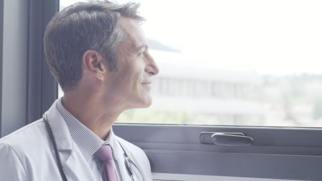 Male doctor reading clipboard by hospital window