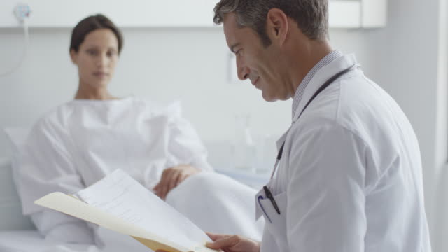 male doctor reading record and talking to patient - examination gown stock videos and b-roll footage
