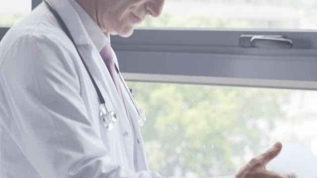 male doctor reviewing medical chart by window - leaning stock videos & royalty-free footage