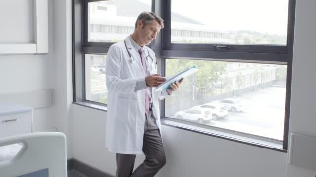 vídeos de stock, filmes e b-roll de médico masculino revisão ficha médica no hospital - quadro médico