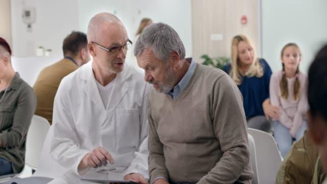 待合室で彼のシニア男性患者の横に座って、彼にタブレットでスキャンを示す男性医師