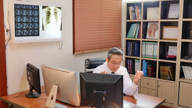 male doctor sitting in his office - schnurloses telefon stock-videos und b-roll-filmmaterial