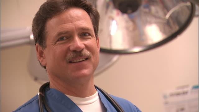 SLO MO, CU, SELECTIVE FOCUS, Male doctor smiling, portrait