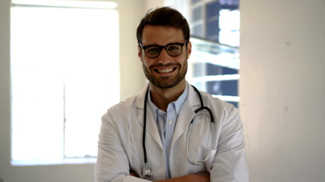 Male doctor standing arms crossed in clinic