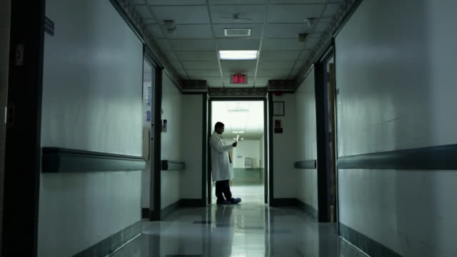 male doctor standing in hospital corridor - korridor stock-videos und b-roll-filmmaterial