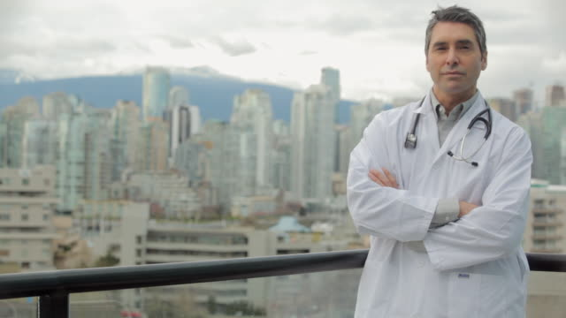 MS PAN Male doctor surgeon standing at balcony of building / Vancouver, BC, Canada