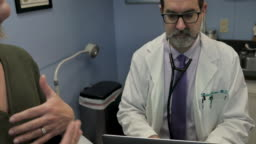 Male doctor taking medical notes on a laptop while a female patient talks
