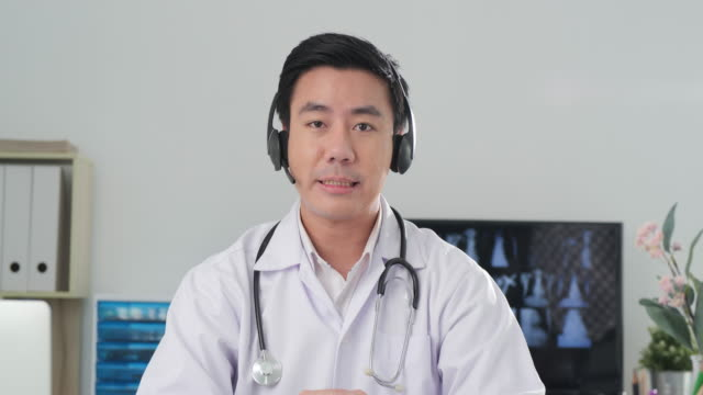 male doctor talking to camera at clinic. - webcam stock videos & royalty-free footage
