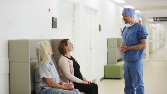 vídeos y material grabado en eventos de stock de médico masculino hablando con mujeres en el hospital - sala de espera característica de edificio