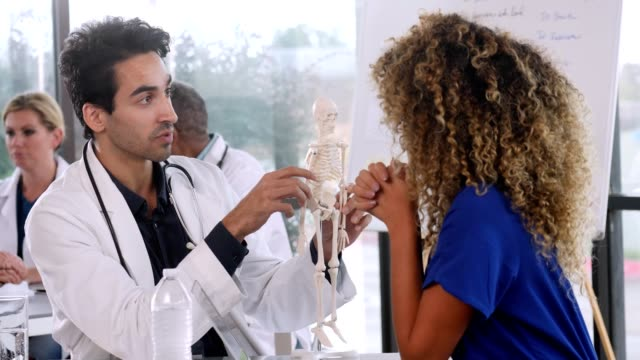 male doctor uses skeleton model while talking with medical student - medical student stock videos and b-roll footage