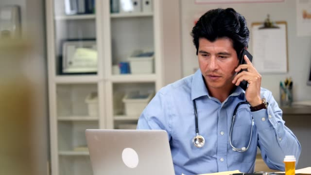 male doctor uses smartphone to consult with a colleage about a patient's diagnosis - prescription medicine stock videos & royalty-free footage