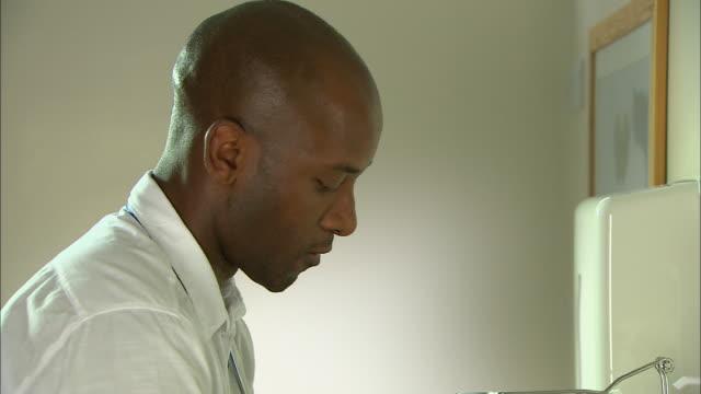 vídeos de stock e filmes b-roll de male doctor washing his hands - porta sabonete líquido
