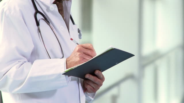 vidéos et rushes de cu, tu, male doctor writing in medical chart in hospital corridor, berlin, germany - seulement des hommes d'âge mûr