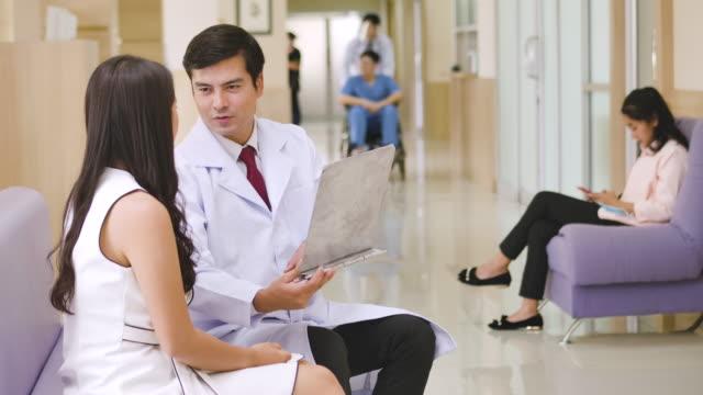 männliche ärzte sprechen mit weiblichen patienten auf soaf im krankenhaus. - rettungsdienst mitarbeiter stock-videos und b-roll-filmmaterial
