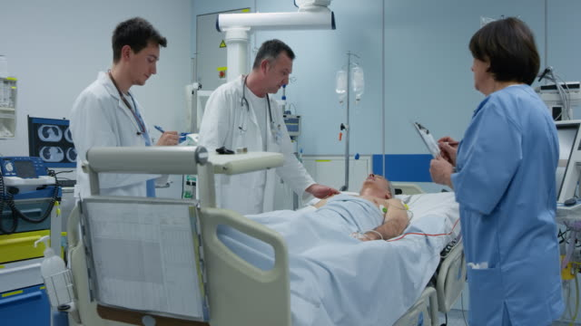 ds male doctors visiting a patient on their round through the icu - ward stock videos & royalty-free footage
