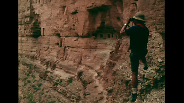 male dressed in shorts amp safari hard hat standing cliff side w/ cliff dweller dwelling cavate house carved openings in rock bg reverse pan cliff ws... - cliff dwelling stock videos & royalty-free footage