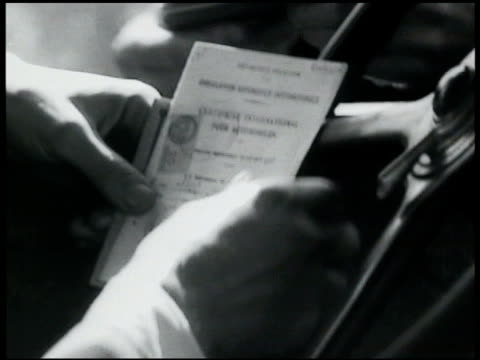 vidéos et rushes de male driver hands handing united states passport other papers to policeman hands through car window - 1935