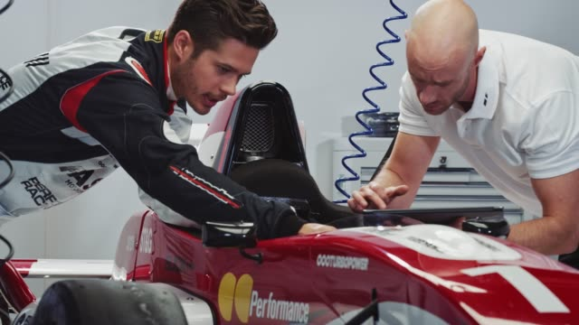 male driver is examining racecar with mechanic - motorsport stock videos & royalty-free footage