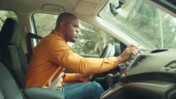 Male driver using smartphone for gps navigation in car