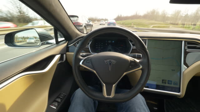 pov male driving fast in a self steering tesla car down an asphalt freeway cool shot of speeding along the highway in a technologically advanced... - driverless car stock videos & royalty-free footage
