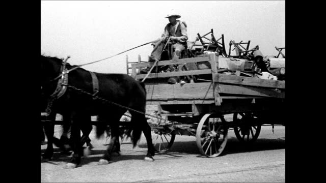 vidéos et rushes de male driving horse drawn wagon loaded w/ belongings furniture family family loading up truck w/ sign 'california or bust' dust bowl refugees man... - tempête de poussière