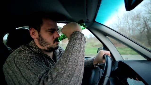 vídeos de stock, filmes e b-roll de motorista bêbado masculina com garrafa de cerveja no carro - motorista ocupação