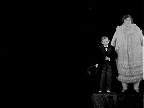 male dwarf accompanied by large woman both standing on pedestal against black background / two young women standing back to back / shirtless man... - sockel stock-videos und b-roll-filmmaterial