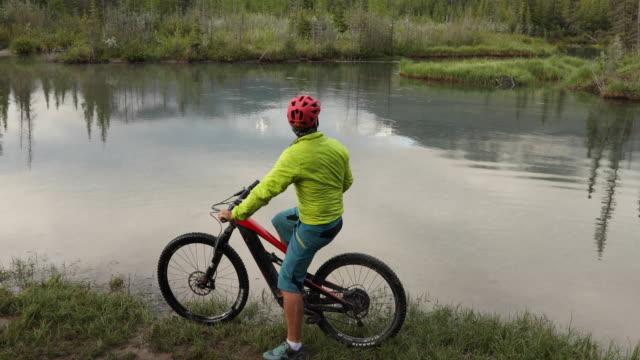 vídeos y material grabado en eventos de stock de paseos e-biker masculinos a lo largo del borde del arroyo de la montaña - one senior man only