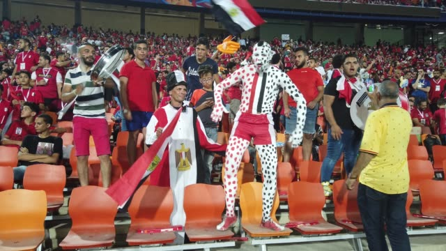 vidéos et rushes de male egypt fan covered in body paint of the egyptian colours dances to music and drumming before the 2019 african cup of nations group a match... - ambiance format raw