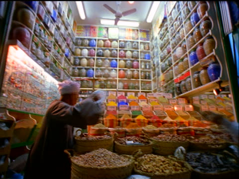 pan male egyptian storekeeper in brightly colored spice store conducting business with man / egypt - spice stock videos & royalty-free footage