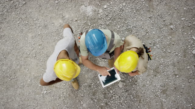 CS Male electrician holding a tablet and talking to a male and female worker and checking the plans