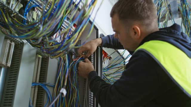 male electrician organizing wires in the ac enclosure - electrical equipment video stock e b–roll