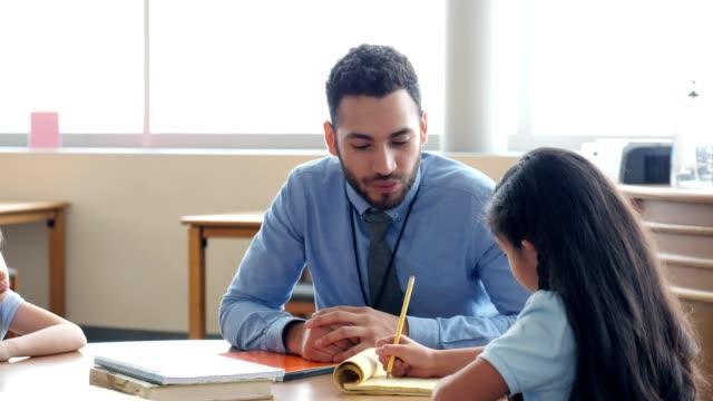 男性小学校教師は女子学生を助ける - note pad点の映像素材/bロール