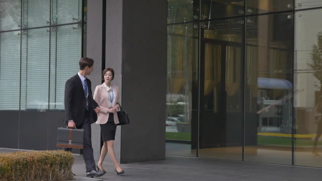 a male employee and a female employee having a conversation while walking - hemd und krawatte stock-videos und b-roll-filmmaterial