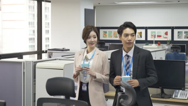 vidéos et rushes de a male employee and a female employee holding cups of coffee - chemise et cravate