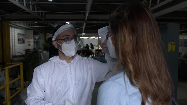 vídeos de stock, filmes e b-roll de funcionário do sexo masculino verificando temperatura e pulverizando álcool nas mãos de funcionários que entram em uma fábrica têxtil - medindo
