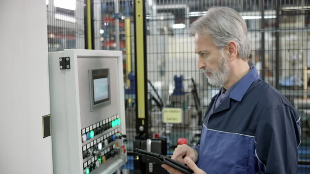 male employee in a factory reading data from the tablet and entering it into a machine using a touch screen - image stock videos & royalty-free footage