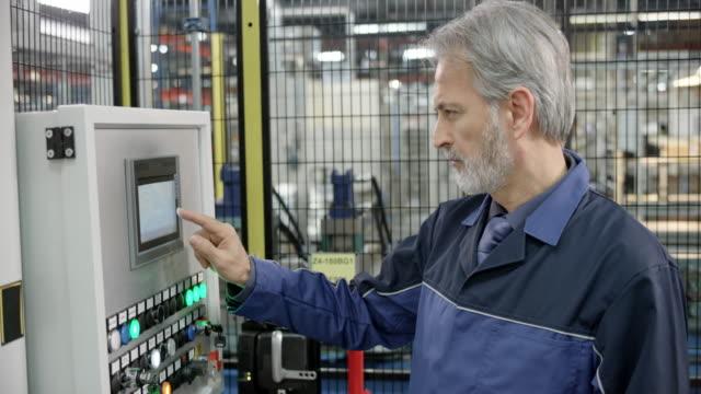 vídeos y material grabado en eventos de stock de hombre empleado en una fábrica con una pantalla táctil para introducir datos en una máquina - manufacturing machinery