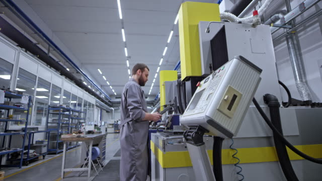 cs male employee operating a machine in the factory - control stock videos & royalty-free footage
