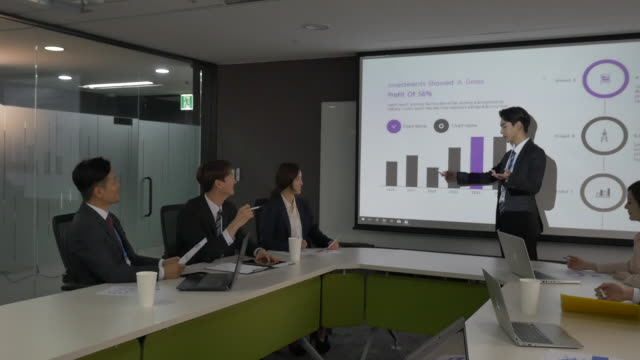 a male employee presenting a powerpoint at a company meeting - east asia stock videos & royalty-free footage