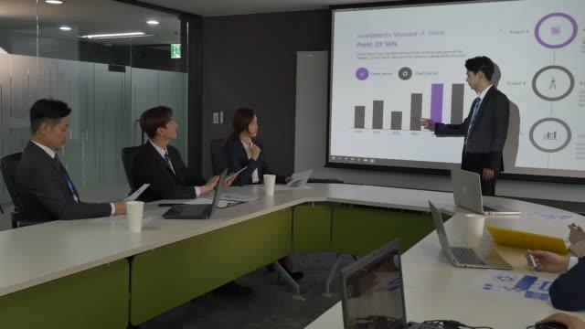 vidéos et rushes de a male employee presenting a powerpoint at a company meeting - chemise et cravate
