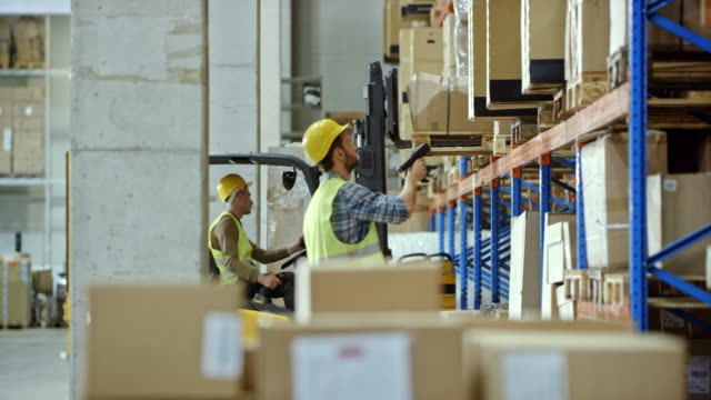 male employee scanning packages in the warehouse - forklift truck stock videos and b-roll footage