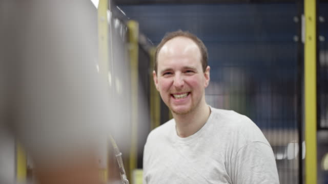 Male employee smiling while doing his job in the factory