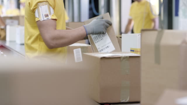 ld male employee sorting packages on the conveyor belt - belt stock videos and b-roll footage