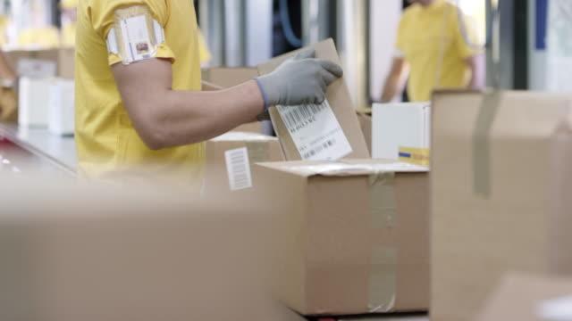 並べ替えコンベア ベルトにパッケージ ld 男性従業員 - コンベヤーベルト点の映像素材/bロール