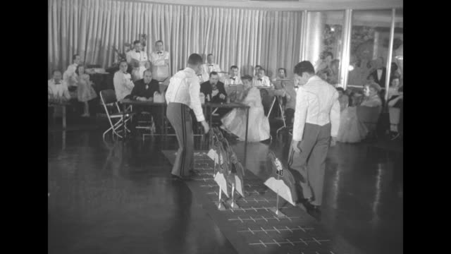 vídeos de stock, filmes e b-roll de vs male employees moving horses on a rectangular board on the floor with the ship's band looking on formally dressed passengers applaud / vs the... - copo de cerveja