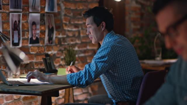 r/f manliga anställda jobbar sent bakom deras kontorsbord - 30 34 ��r bildbanksvideor och videomaterial från bakom kulisserna