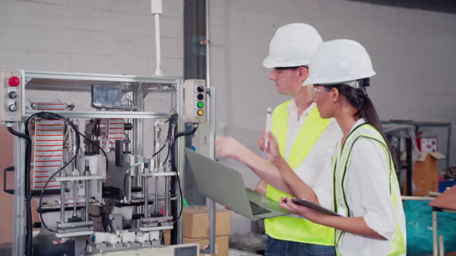 male engineer and female engineer talking about maintenance or installation of machines in a production process, a man aged 30-40 holds a computer with a woman holding a tablet standing next to the machine. - man and machine stock videos & royalty-free footage